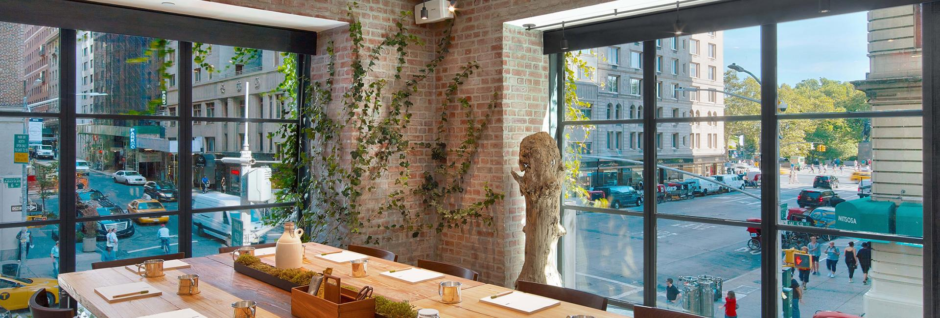 A long wooden dinner table in a room with windows overlooking NYC streets.