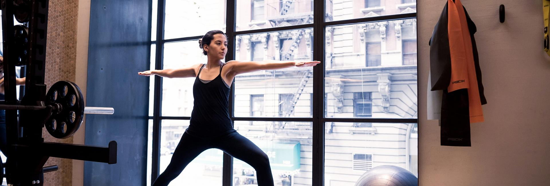 woman doing yoga in a gym with floor to ceiling windows