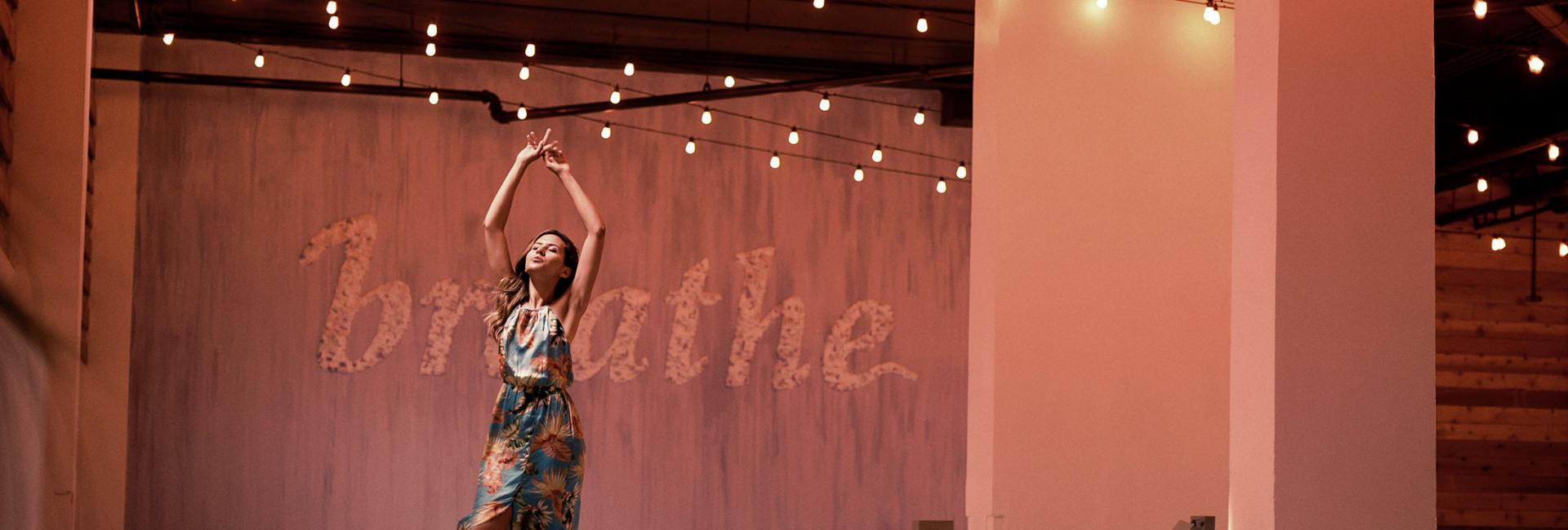 A woman dancing in a room decorated with twinkle lights