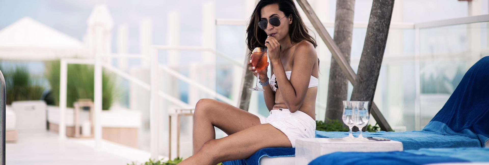 Woman sipping cocktail by the pool