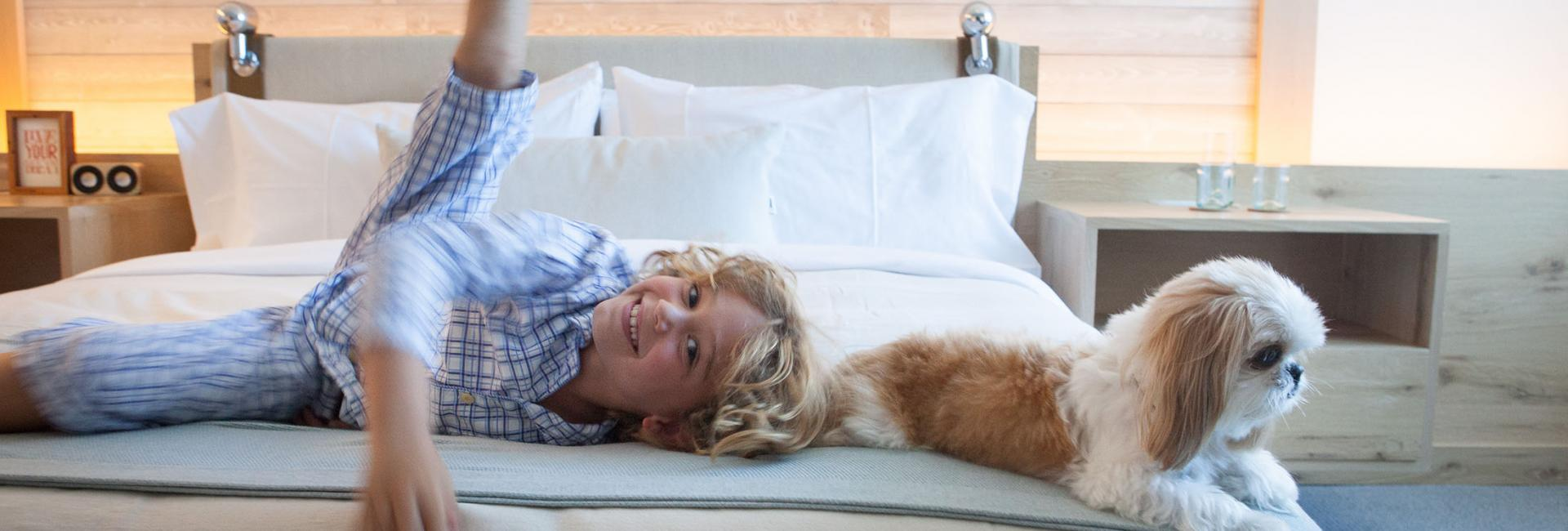 A little boy playing on a bed with a small dog