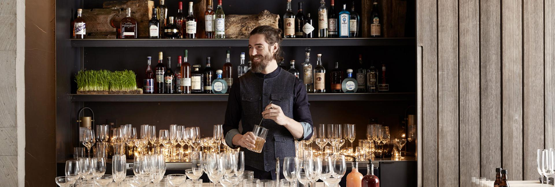 Bartender making cocktail in front of fancy bar