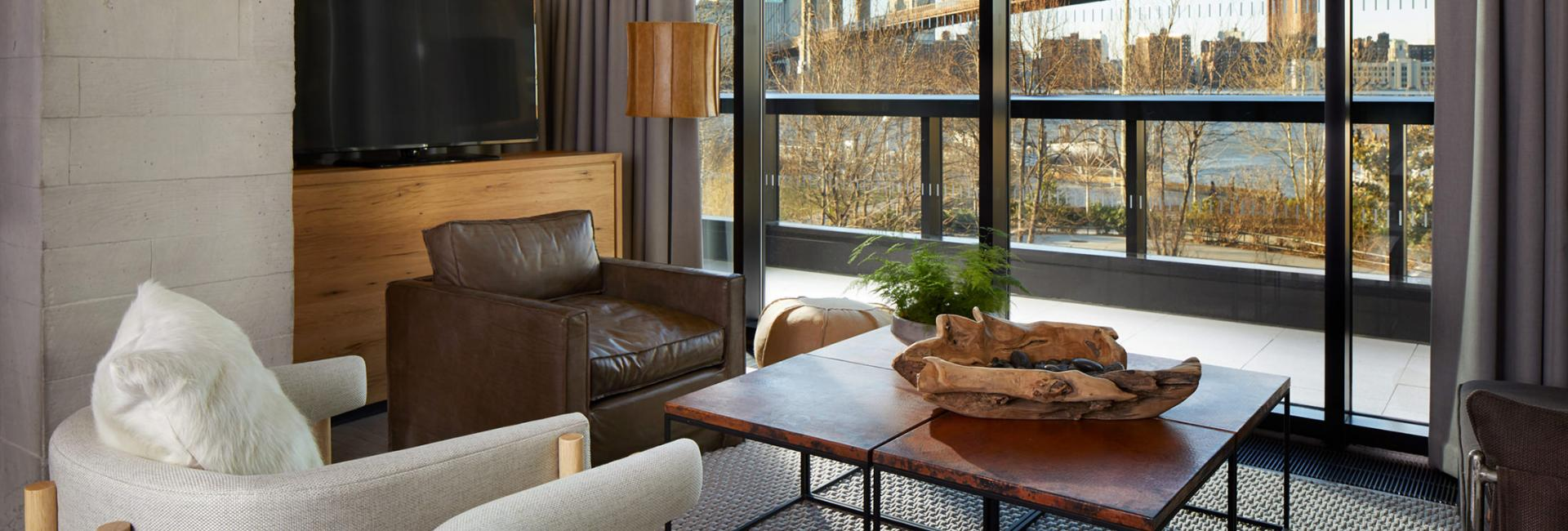 The lounge area of a 1 Hotels suite with a view of Brooklyn Bridge.