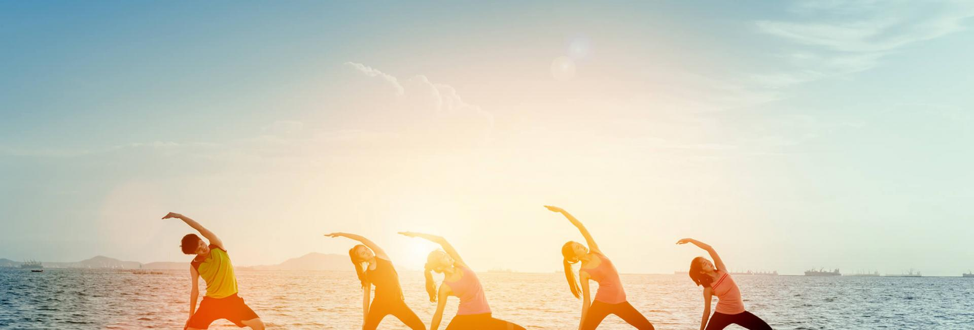 group doing yoga on the beach
