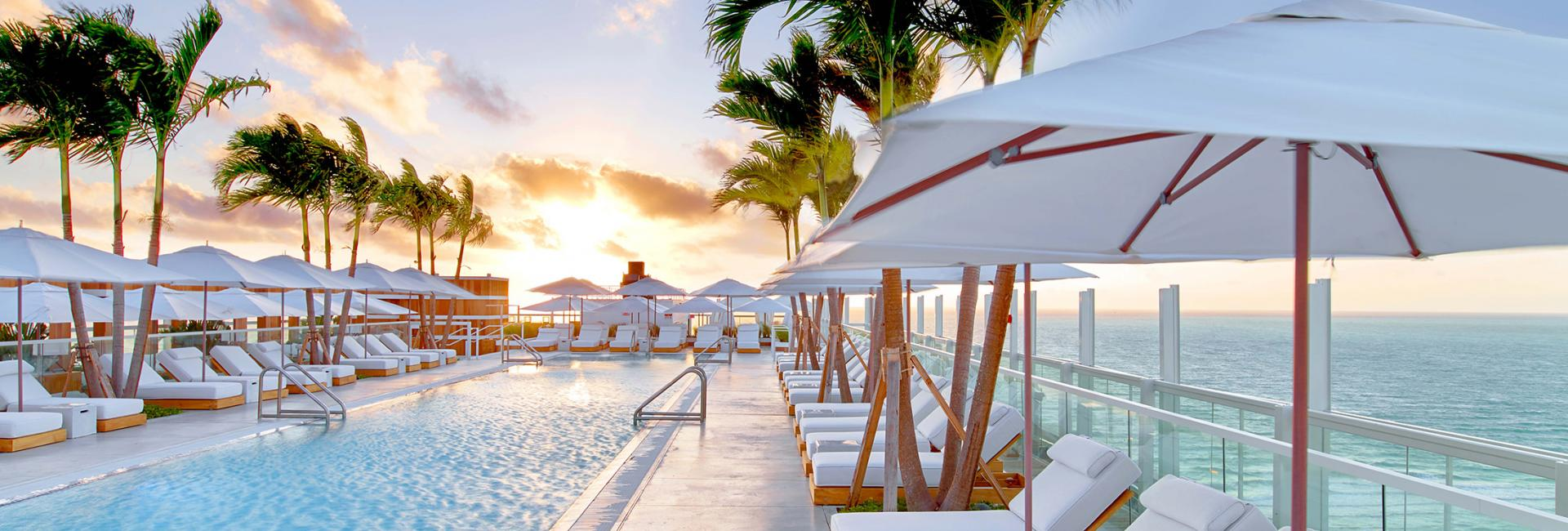 The sun rising over the pool and white lounge chairs at 1 Hotel South Beach.