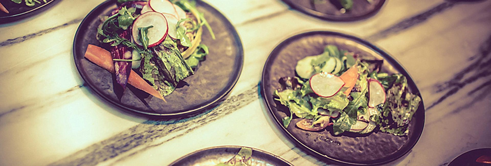 A close-up of plated side garden salads on a wooden table.