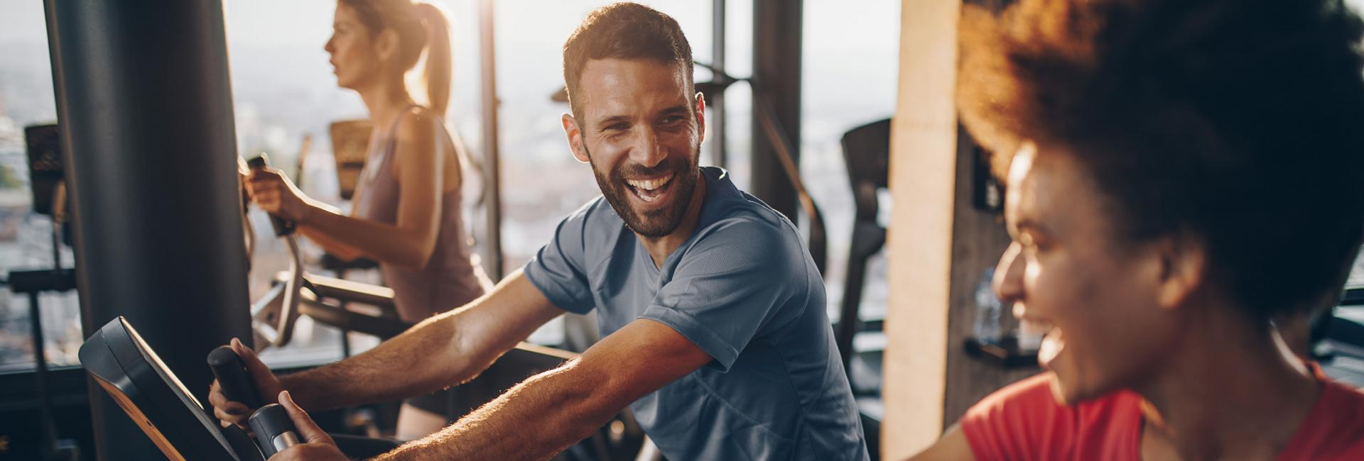 man and woman smile while on exercise bikes