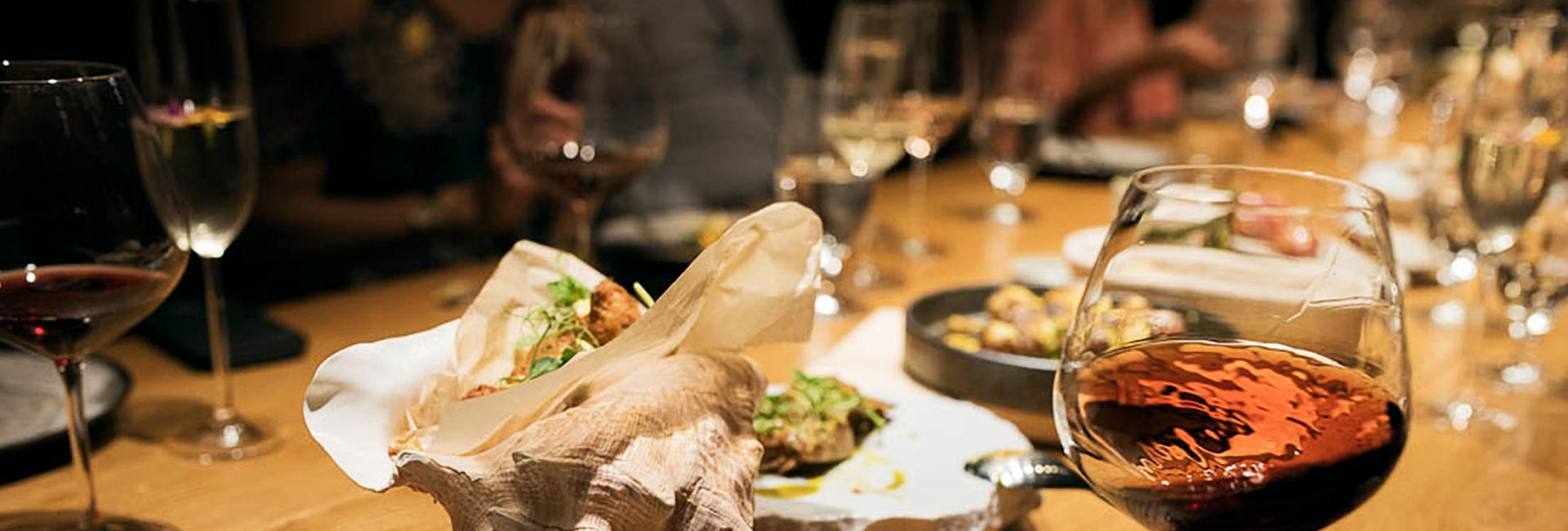 Conch shell on table with glass of red wine