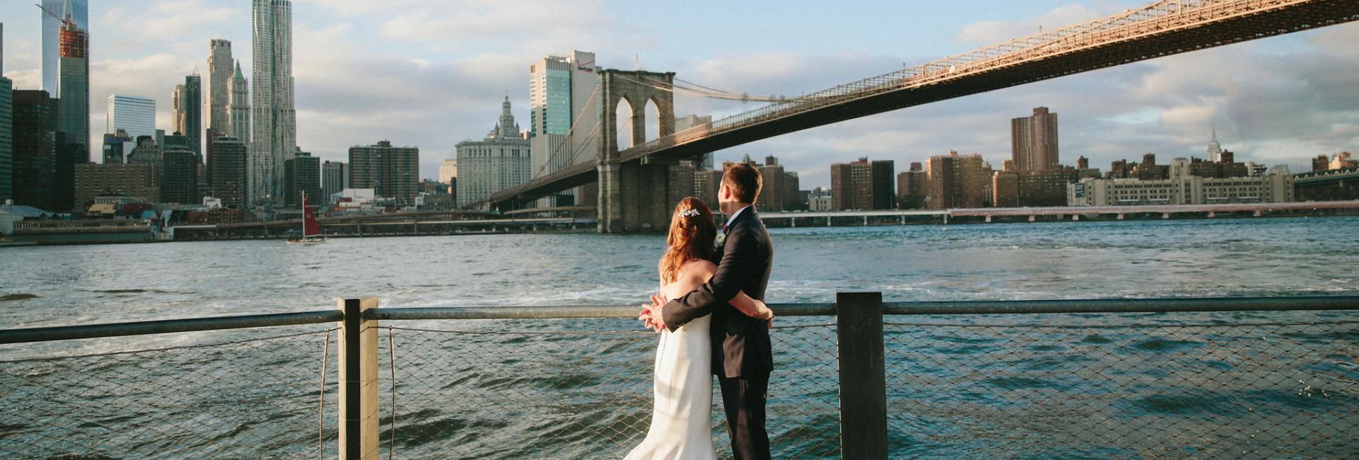 Couple stands on waterfront near brooklyn bridge in wedding attire