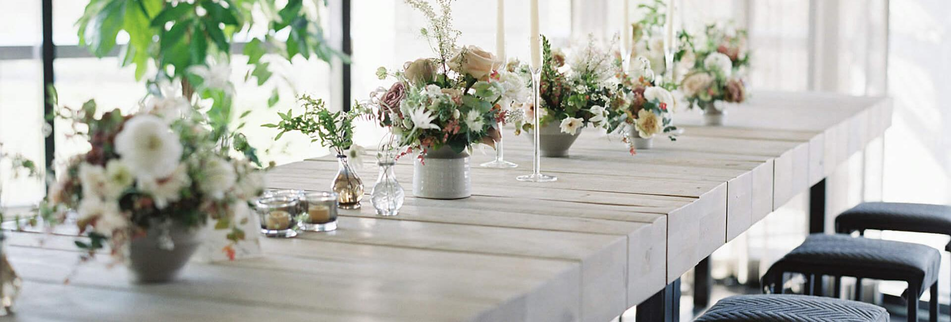 A row of tables decorated with wedding florals and tealights.