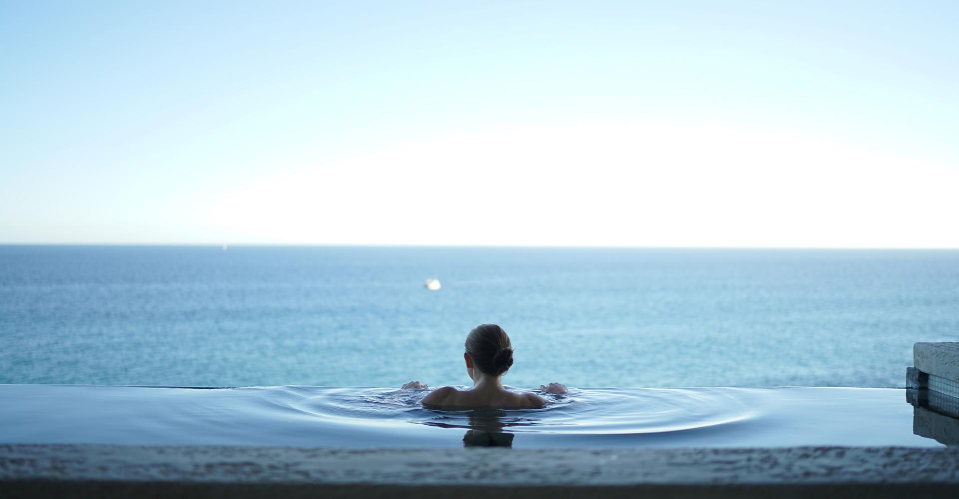 woman in pool overlooking the ocean in cabo