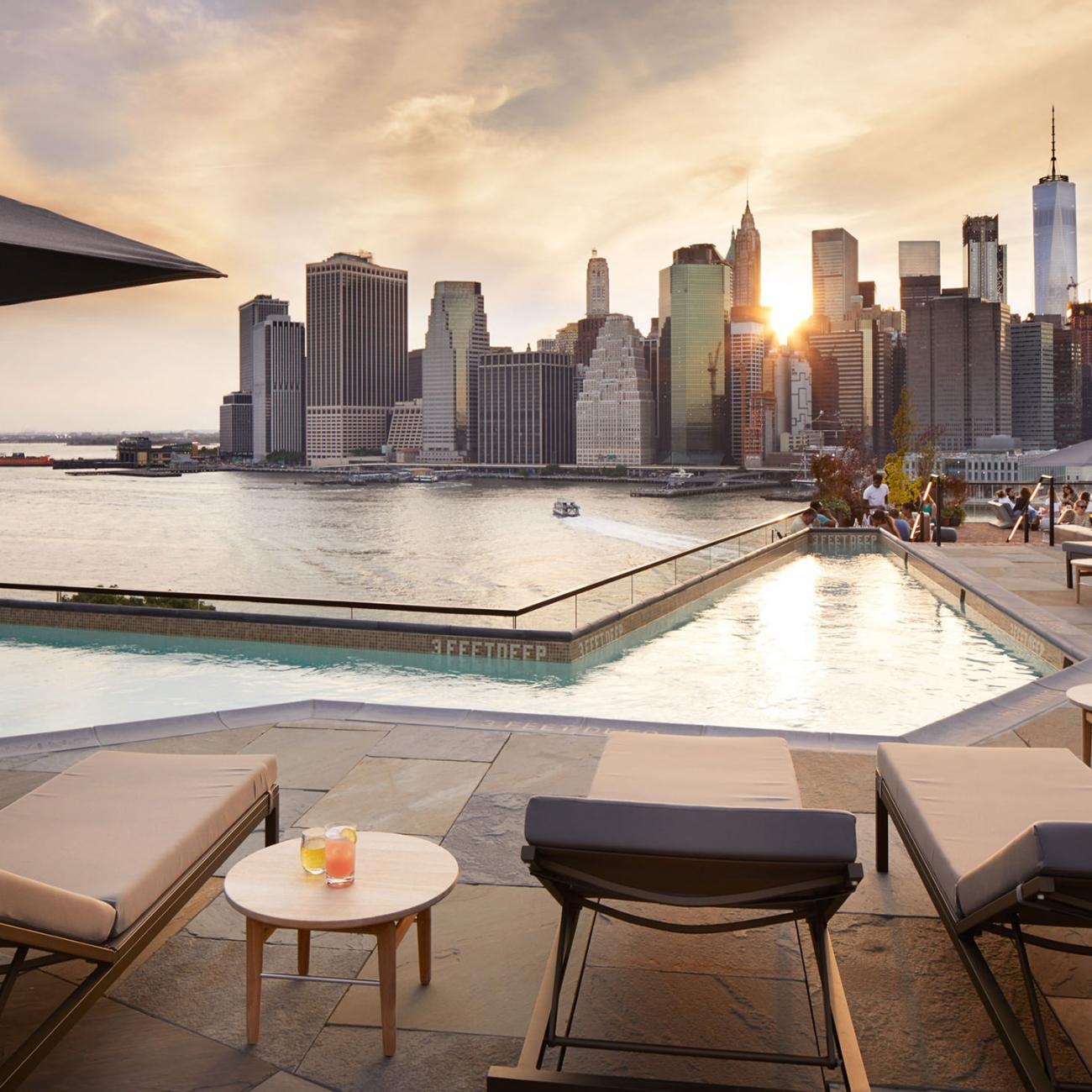 View of skyline next to pool at rooftop brooklyn bridge