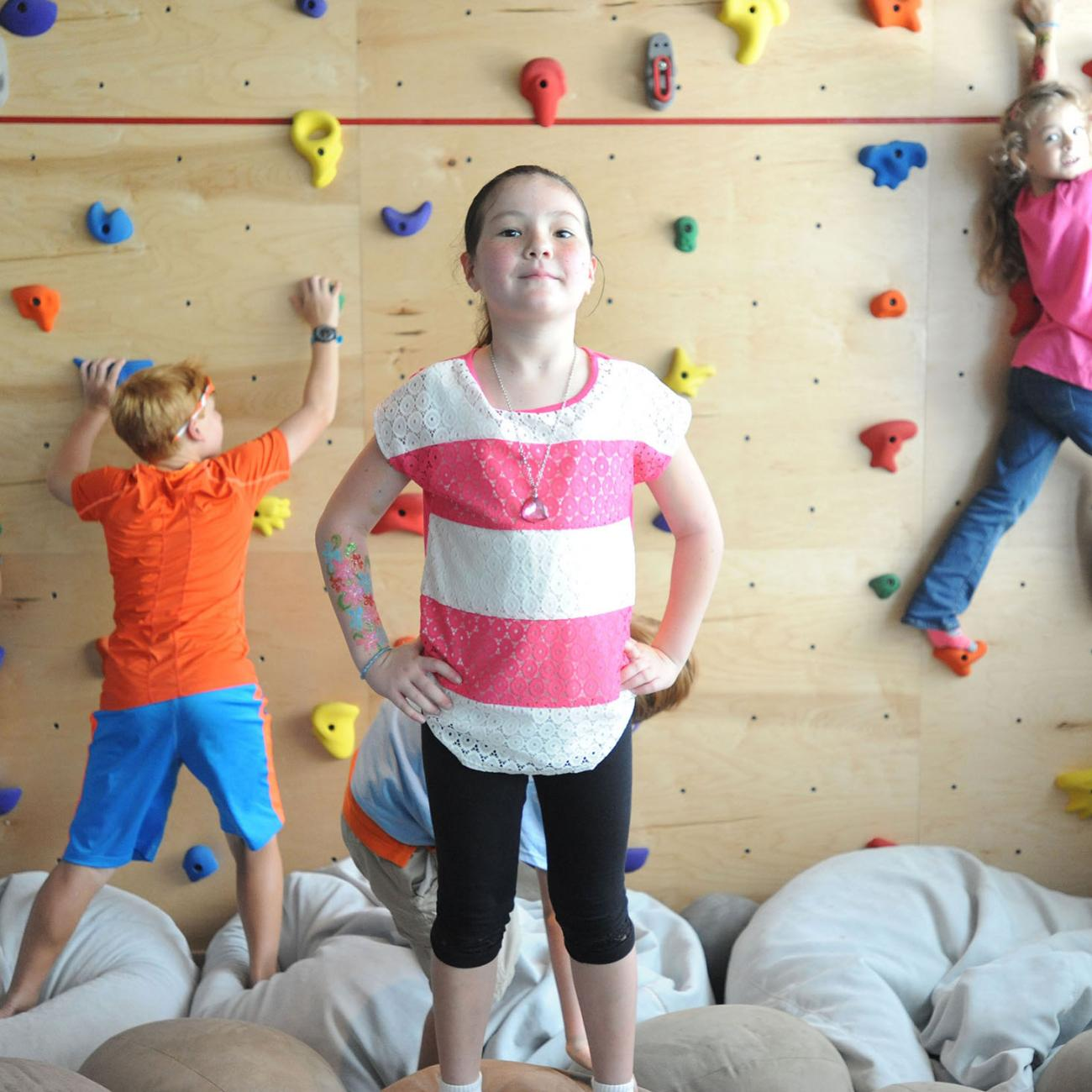 A young girl standing confidently in front of a rock climbing wall