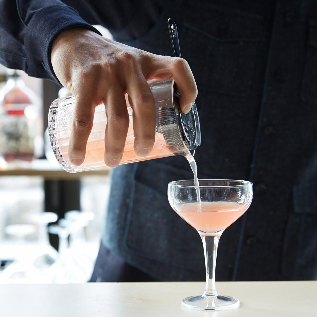 A man pouring a light pink cocktail from a shaker into a glass