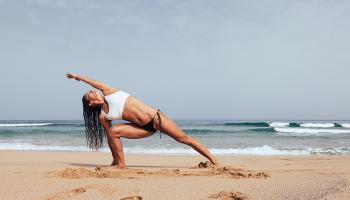A woman does yoga on a beach
