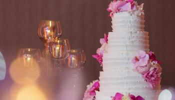 A tall white wedding cake decorated with pink flowers