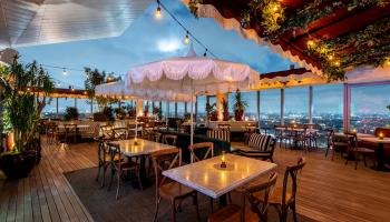 Tables lit up on a rooftop bar overlooking West Hollywood